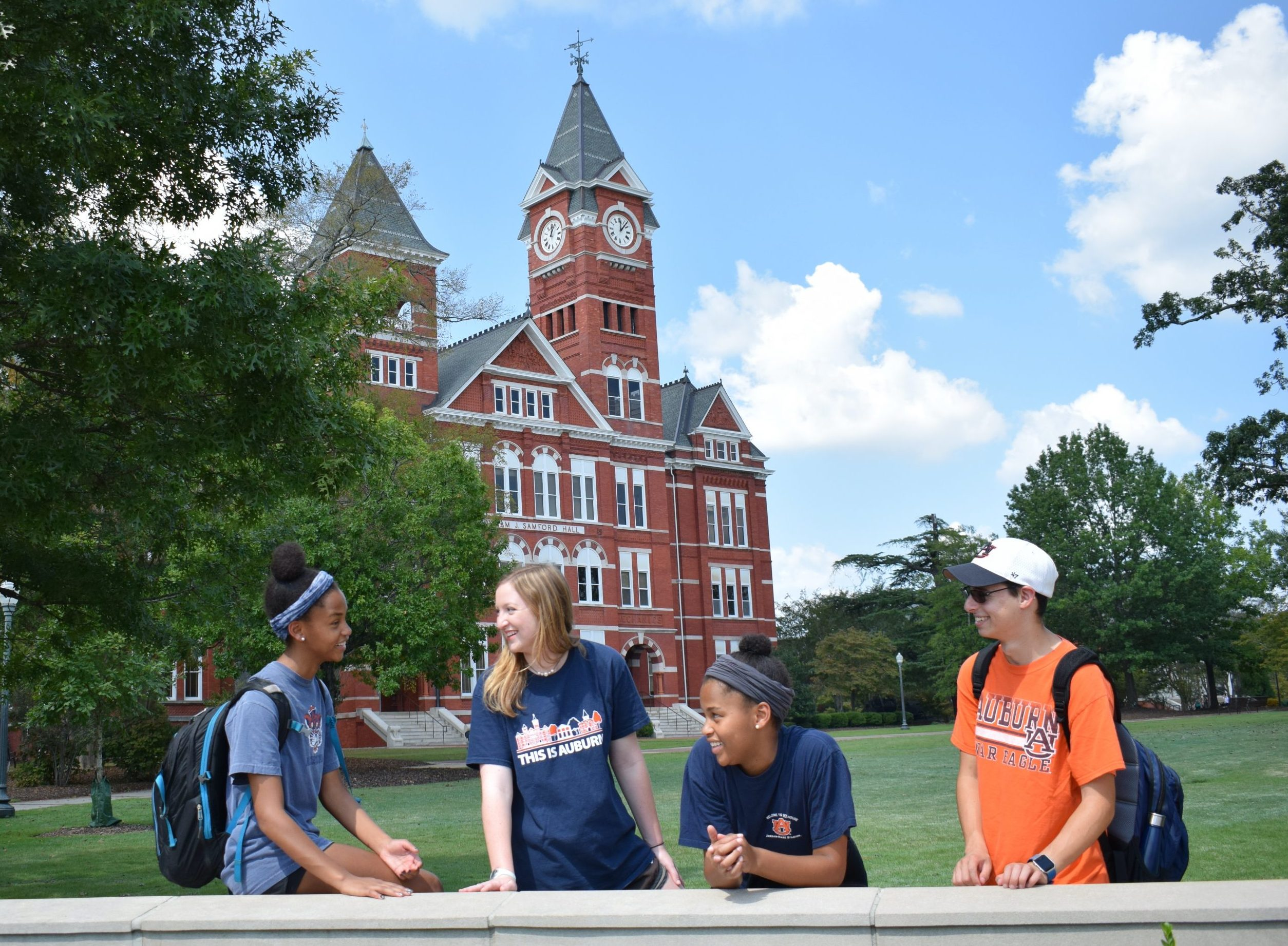 Picture four Auburn students talking in front of Samford Hall on Auburn's Campus