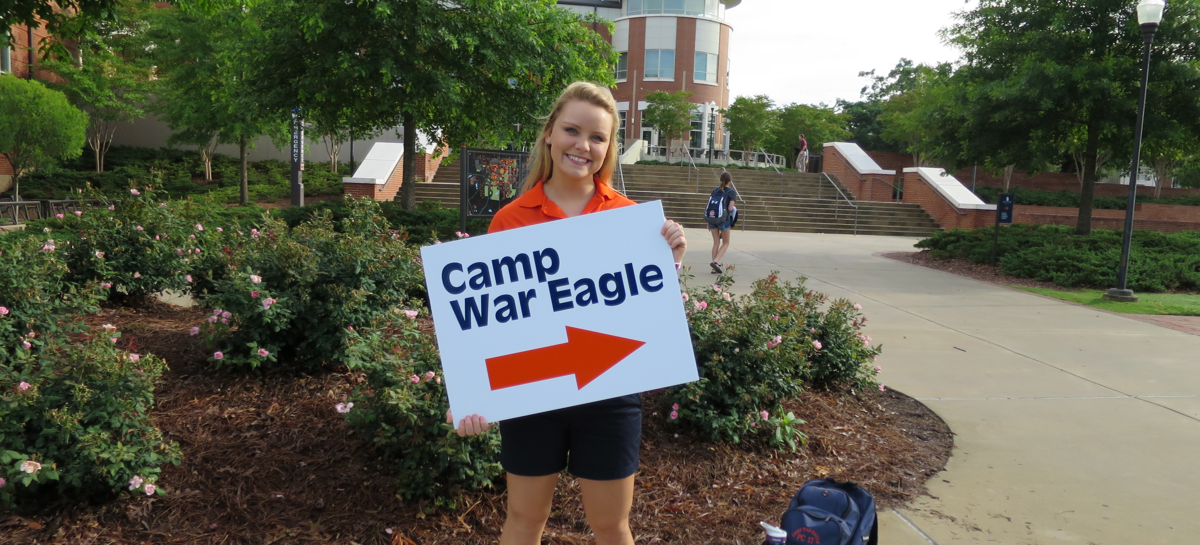 Camp War Eagle Counselor holding sign